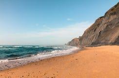 Μια εγκαταλειμμένη παραλία με τον ηφαιστειακό απότομο βράχο και τα γαλαζοπράσινα νερά του Ατλαντικού Ωκεανού σε Sagres, Algarves, Στοκ Φωτογραφία