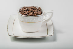 Μια εικόνα ενός φλυτζανιού γέμισε με τα φασόλια καφέ Στοκ Εικόνες