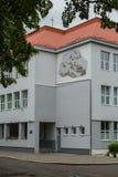 Μια εικόνα στον τοίχο ενός κτηρίου με μια κεραμωμένη στέγη και μια σημαία της χώρας σε ένα κοντάρι σημαίας Στοκ Εικόνες
