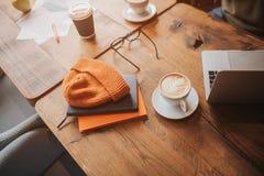 Μια εικόνα του σύγχρονου minimalistic πίνακα με κάποια ποτά, ενδύματα και lap-top σε το Άποψη περικοπών στοκ εικόνα