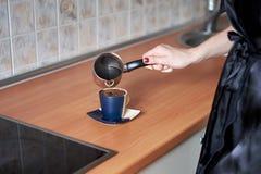 Μια εικόνα των νέων γυναικών που προετοιμάζουν τον καφέ στην κουζίνα το πρωί Στοκ Φωτογραφίες