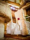 Μια εικόνα των floral ρυθμίσεων που βρίσκονται στα καθίσματα σε μια γαμήλια τελετή Στοκ Εικόνες