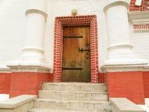 Μια εκλεκτής ποιότητας καφετιά πόρτα στον άσπρο και κόκκινο τοίχο στοκ φωτογραφίες
