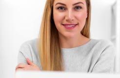 Μια ελκυστική γυναίκα εξετάζει τη κάμερα καθμένος στο γραφείο στον εργασιακό χώρο ή στο σπίτι Κάθισμα στο γραφείο Στοκ φωτογραφία με δικαίωμα ελεύθερης χρήσης