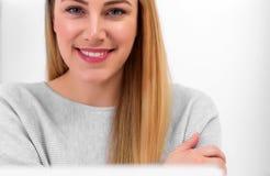 Μια ελκυστική γυναίκα εξετάζει τη κάμερα καθμένος στο γραφείο στον εργασιακό χώρο ή στο σπίτι Κάθισμα στο γραφείο Στοκ Εικόνες