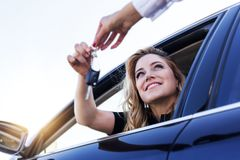 Μια ελκυστική γυναίκα σε ένα αυτοκίνητο παίρνει τα κλειδιά αυτοκινήτων Μίσθωμα ή αγορά του αυτοκινήτου στοκ εικόνες