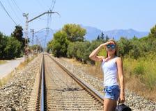 Μια ελκυστική νέα γυναίκα με τη μακριά καφετιά τρίχα που περπατά κοντά στο σιδηρόδρομο στοκ εικόνα με δικαίωμα ελεύθερης χρήσης