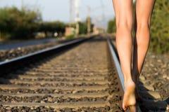 Μια ελκυστική νέα γυναίκα με τη μακριά καφετιά τρίχα που περπατά κοντά στο σιδηρόδρομο στοκ εικόνες