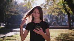 Μια ελκυστική νέα κυρία που χρησιμοποιεί ένα τηλέφωνο στην πόλη Μέσος πυροβολισμός απόθεμα βίντεο