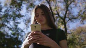 Μια ελκυστική νέα κυρία που χρησιμοποιεί ένα τηλέφωνο στην πόλη Μέσος πυροβολισμός φιλμ μικρού μήκους