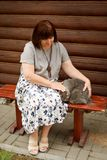 Μια ενήλικη παχουλή γυναίκα κάθεται σε έναν πάγκο κοντά σε ένα σπίτι κούτσουρων και κτυπά μια γκρίζα γάτα Στοκ εικόνα με δικαίωμα ελεύθερης χρήσης