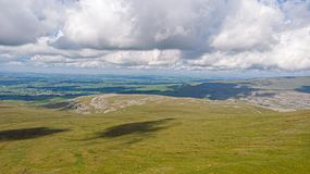 Μια εναέρια άποψη μιας κοιλάδας βουνών με την πράσινη κλίση και του αγροτικού χωριού στο υπόβαθρο κάτω από έναν θυελλώδη άσπρο ου στοκ εικόνα με δικαίωμα ελεύθερης χρήσης