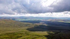 Μια εναέρια άποψη μιας κοιλάδας βουνών με την πράσινη κορυφή κλίσεων και βουνών κυμαίνεται στο υπόβαθρο κάτω από έναν μεγαλοπρεπή στοκ εικόνες με δικαίωμα ελεύθερης χρήσης