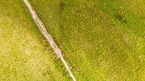 Μια εναέρια άποψη μιας πράσινης κλίσης βουνών με μια πορεία ιχνών, σύσταση υποβάθρου στοκ φωτογραφία