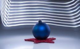 Μια ενιαία μπλε σφαίρα χριστουγεννιάτικων δέντρων ελαφριά αποτελέσματα ενός στα σκοτεινά γκρίζα υποβάθρου Στοκ εικόνα με δικαίωμα ελεύθερης χρήσης