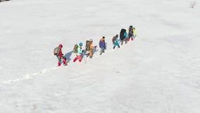 Μια εξοπλισμένη καλά ομάδα κούρασης τουριστών προετοιμάζω το έδαφος, φωτεινή χειμερινή ημέρα, μέσω του χιονιού, χρησιμοποιώντας τ φιλμ μικρού μήκους