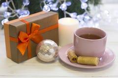 Μια εορταστική ακόμα ζωή με το τσάι, ένα καίγοντας κερί και ένα giftbox Στοκ Φωτογραφίες
