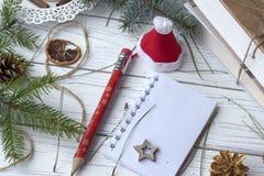 Μια εορταστική χλεύη επάνω στη φωτογραφία με τους κλαδίσκους έλατου, ένα ανοιγμένο βιβλίο σημειώσεων, ένα παλαιό βιβλίο, ένα μολύ Στοκ εικόνα με δικαίωμα ελεύθερης χρήσης