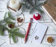 Μια εορταστική χλεύη επάνω στη φωτογραφία με τους κλαδίσκους έλατου, ένα ανοιγμένο βιβλίο σημειώσεων, ένα παλαιό βιβλίο, ένα μολύ Στοκ Εικόνα