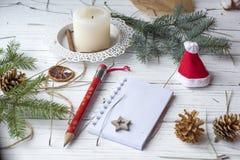 Μια εορταστική χλεύη επάνω στη φωτογραφία με τους κλαδίσκους έλατου, ένα ανοιγμένο βιβλίο σημειώσεων, ένα παλαιό βιβλίο, ένα μολύ Στοκ φωτογραφία με δικαίωμα ελεύθερης χρήσης