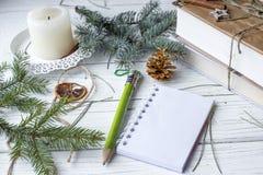 Μια εορταστική χλεύη επάνω στη φωτογραφία με τους κλαδίσκους έλατου, ένα ανοιγμένο βιβλίο σημειώσεων, ένα παλαιό βιβλίο, ένα μολύ Στοκ Εικόνες