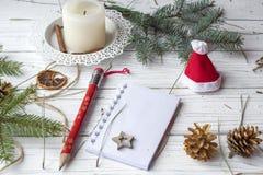 Μια εορταστική χλεύη επάνω στη φωτογραφία με τους κλαδίσκους έλατου, ένα ανοιγμένο βιβλίο σημειώσεων, ένα παλαιό βιβλίο, ένα μολύ Στοκ Φωτογραφία