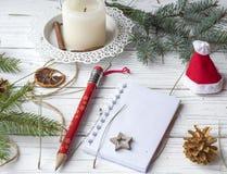 Μια εορταστική χλεύη επάνω στη φωτογραφία με τους κλαδίσκους έλατου, ένα ανοιγμένο βιβλίο σημειώσεων, ένα παλαιό βιβλίο, ένα μολύ Στοκ εικόνες με δικαίωμα ελεύθερης χρήσης