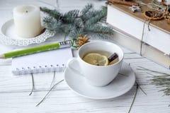 Μια εορταστική χλεύη επάνω στη φωτογραφία με τους κλαδίσκους ενός έλατου, ένα ανοιγμένο βιβλίο σημειώσεων, ένα παλαιό βιβλίο, ένα Στοκ Εικόνες