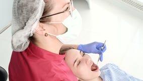 Μια επαγγελματική γυναίκα οδοντιάτρων στα γυαλιά και τις φόρμες εξετάζει τη στοματική κοιλότητα ενός νέου κοριτσιού στην οδοντική απόθεμα βίντεο