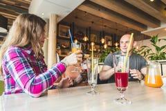 Μια επιχείρηση των νέων που έχουν τη διασκέδαση, πίνοντας τα ποτά, κοκτέιλ, χυμοί σε έναν καφέ Καλύτεροι φίλοι συνεδρίασης στοκ εικόνα