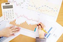 Μια επιχειρηματίας που αναλύει την έκθεση σχετικά με το διάγραμμα με τον υπολογιστή Στοκ Εικόνες