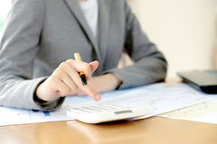 Μια επιχειρηματίας που αναλύει την έκθεση σχετικά με το διάγραμμα με τον υπολογιστή Στοκ φωτογραφία με δικαίωμα ελεύθερης χρήσης