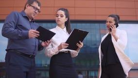 Μια επιχειρησιακή γυναίκα εξετάζει τα έγγραφα εργασίας ενώ ένας επιχειρηματίας και μια επιχειρησιακή γυναίκα την φροντίζουν HD απόθεμα βίντεο