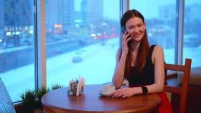 Μια επιχειρησιακή γυναίκα κάθεται σε έναν καφέ και χαμογελά και μιλά στο τηλέφωνο απόθεμα βίντεο