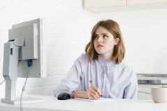 Μια επιχειρησιακή γυναίκα κάθεται στο γραφείο με έναν υπολογιστή και ένα γράψιμο Ένας στο γραφείο στο ύφος σοφιτών Στοκ φωτογραφίες με δικαίωμα ελεύθερης χρήσης