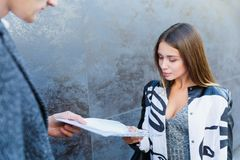 Μια επιχειρησιακή νέα γυναίκα παραδίδει ένα έγγραφο σε έναν άνδρα στοκ εικόνα