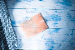 Μια ετικέττα κοντά σε ένα πλεκτό μαντίλι σε ένα άσπρο ξύλινο υπόβαθρο Στοκ εικόνα με δικαίωμα ελεύθερης χρήσης