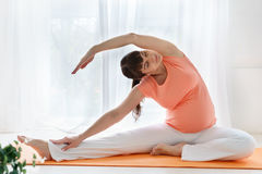 Μια ευρωπαϊκή έγκυος γυναίκα με ρόδινη tshirt do yoga ασκεί για το carehealth της και το αγέννητο παιδί στην ελαφριά κρεβατοκάμαρ Στοκ Εικόνες