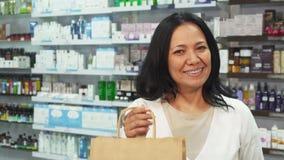 Μια ευτυχής γυναίκα κρατά μια τσάντα αγορών και μια πιστωτική κάρτα φιλμ μικρού μήκους