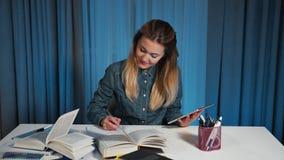 Μια ευτυχής γυναίκα σπουδαστής σε ένα πουκάμισο τζιν, χρησιμοποιεί μια ταμπλέτα και ξαναγράφει τις πληροφορίες σε ένα εγχειρίδιο απόθεμα βίντεο