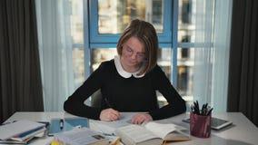 Μια ευτυχής μαθήτρια παίρνει μια ιδέα και αρχίζει σε ένα σημειωματάριο να κάνει την εργασία camera smiling απόθεμα βίντεο