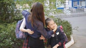 Μια ευτυχής μητέρα συναντά δύο κόρες της από το σχολείο Το Mom αγκαλιάζει και φιλά τα παιδιά της στη σχολική στολή απόθεμα βίντεο