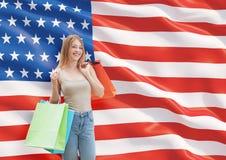 Μια ευτυχής νέα γυναίκα με τις ζωηρόχρωμες τσάντες αγορών από τα φανταχτερά καταστήματα Στοκ Φωτογραφίες