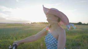 Μια ευτυχής νέα γυναίκα σε ένα καπέλο οδηγά μια αναδρομική μοτοσικλέτα και απολαμβάνει έναν γύρο σε έναν βρώμικο δρόμο μεταξύ των απόθεμα βίντεο