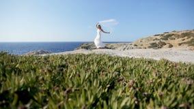 Μια ευτυχής νύφη στέκεται στην ακτή κάτω από ένα γαμήλιο πέπλο που κυματίζει στον αέρα Η έννοια ενός ευτυχών γάμου και ενός α απόθεμα βίντεο