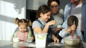 Μια ευτυχής οικογένεια πέντε μαγείρων στην κουζίνα Τα παιδιά παίζουν με το αλεύρι, mom γέλια Κίνηση Slown φιλμ μικρού μήκους