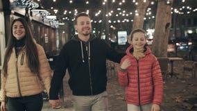 Μια ευτυχής οικογένεια περπατά το βράδυ στην πόλη στις διακοπές φιλμ μικρού μήκους