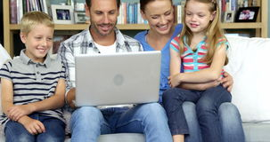 Μια ευτυχής οικογένεια που απολαμβάνει μια στιγμή με έναν υπολογιστή απόθεμα βίντεο