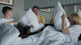 Μια ευτυχής χαμογελώντας οικογένεια σε ένα κρεβάτι με ένα παιχνίδι μαξιλαριών σε ένα κρεβάτι με τα άσπρα φύλλα Η έννοια μιας ευτυ απόθεμα βίντεο