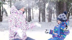 Μια ευτυχή μητέρα και ένα παιδικό παιχνίδι στο χιόνι, που ρίχνει το επάνω καθμένος μπροστά από ένα χειμερινό δάσος ή ένα πάρκο Φω φιλμ μικρού μήκους